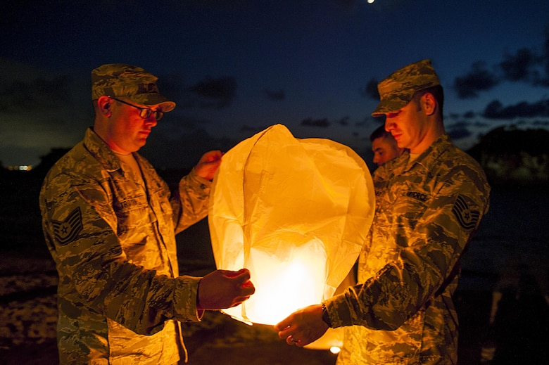 U.S. Air Force Tech. Sgt. Ezequiel Rodriguez, 18th Operations Support Squadron NCO in charge of airfield management and Tech. Sgt. Dustin Troyer, 18th OSS deputy airfield manager, prepare to launch a sky lantern during the POW/MIA Sky Lantern Ceremony Sept. 17, 2015, at the Kadena Marina, Kadena Air Base, Japan. The lanterns were lit in remembrance of POWs and MIAs. (U.S. Air Force photo by Airman 1st Class Lynette M. Rolen/Released)