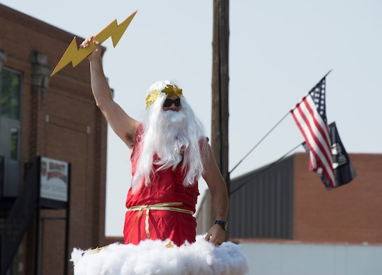 Capt. Curtis Culver, 389th Fighter Squadron pilot, raises a lightning bolt while dressed as Zeus during the Air Force Appreciation Day parade at Mountain Home, Idaho, Sept. 12, 2015. The 389th FS has embraced their name: T-Bolts. (U.S. Air Force photo by Airman Chester Mientkiewicz)