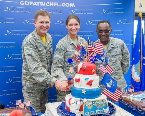 Brig. Gen. Wayne Monteith, 45th Space Wing commander, Airman 1St Class Katie Skrzypczak, 45th Civil Engineer Squadron, youngest Airman, and Lt. Col. Leonid Katkovsky, 45th Aerospace Medical Squadron, oldest Airman, in keeping with the tradition of cutting the Air Force Birthday cake during a celebration at the Patrick Air Force Base Golf Course and Marina, Sept. 18, 2015. (U.S. Air Force photo/Matthew Jurgens/Released)
