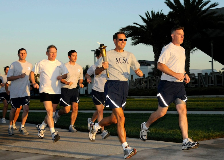 As the sun sets in the West with 54 miles behind them, the POW/MIA torch relay team arrives on the grounds of the Space and Missile Systems Center's Schriever Space Complex at Los Angeles Air Force Base in El Segundo, Calif. Another 100 miles will be pounded out overnight on the running track as each runner executed the same mission – ensuring the torch remained lit to represent the nation's resolve; moving it ever forward to show the promise to those missing warriors and their families. (Courtesy photo/James R. Gill)