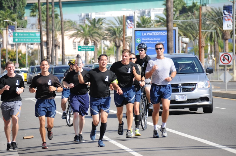 A team of runners from the Space and Missile Systems Center at Los Angeles Air Force Base in El Segundo, Calif. carry the POW/MIA torch on the start of a 24-hour, 154 mile long course through the South Bay beach communities of Los Angeles to honor those who were held captive – and those still missing and unaccounted for during times of armed conflict. (U.S. Air Force photo/Van Ha)