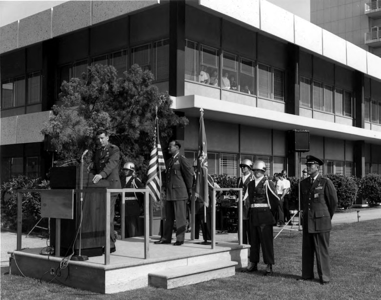 General Bernard A. Schriever, commander of Air Force Systems Command, addresses an assembled crowd in the Area A mall during the dedication of Los Angeles Air Force Station on July 10, 1964. Standing directly behind Gen. Schriever is Maj. Gen. Ben I.Funk, commander of Space Systems Division. Col. Roy Russell, commander of Los Angeles AFS, stands on the far right by the Air Force Honor Guard. (U.S. Air Force photo)