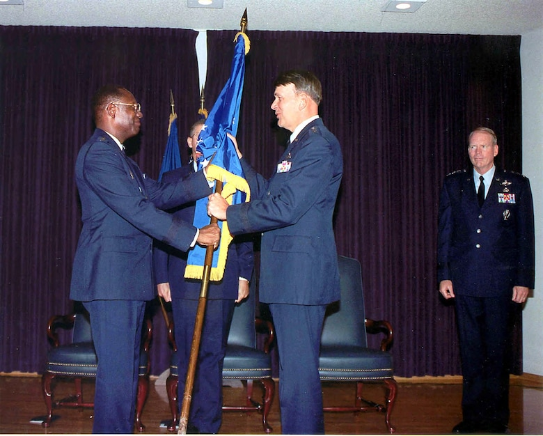 General Lester L. Lyles, commander of Air Force Materiel Command, hands SMC's flag to Lt. Gen. Roger G. DeKok, vice commander of Air Force Space Command, during ceremonies observing SMC's transfer from AFMC to AFSPC in July 1992. Lt. Gen. Brian A. Arnold, commander of SMC, stand at right. Both Lyles and DeKok were former commanders of SMC. (U.S. Air Force photo)