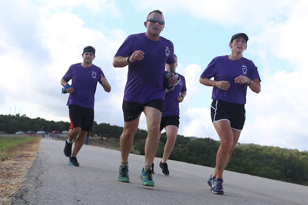 Tyler Goehring, Senior Master Sgt. Daniel Stellabotte, 381st Training Squadron dental lab career development course writer,  and Maj. Sarah Wheeler, 359th Medical Group dentist, run on top of Canyon Lake dam during the Rambler 120 Sept. 19, 2015, at Joint Base San Antonio Recreation Park at Canyon Lake. The Rambler 120, which is hosted by the 502nd force Support Squadron, features four- and eight person teams that engage in a friendly, but third-fought, competition that challenges participants with a 22-mile bike race, 6-mile raft race and a mystery event. (U.S. Air Force photo by Senior Airman Alexandria Slade/Released)