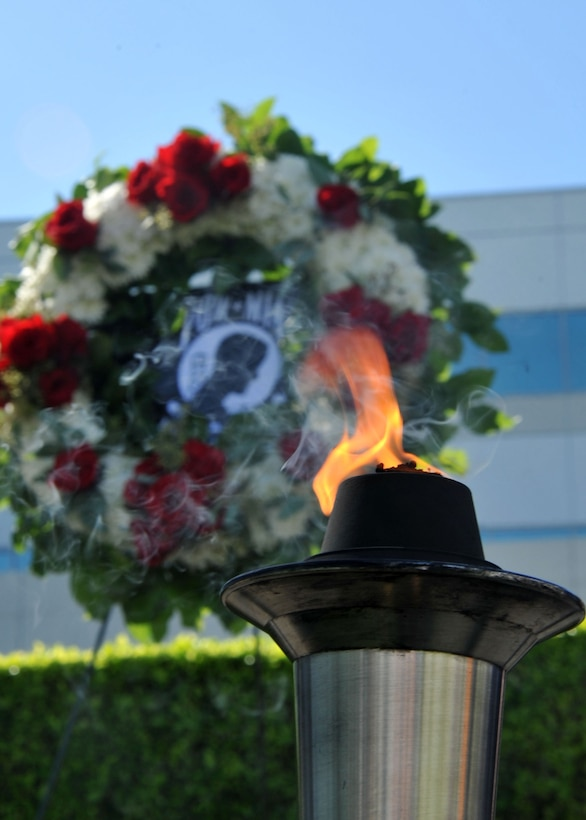 The POW/MIA wreath and torch lie in repose on the stage during the National POW/MIA Recognition Day ceremony Sept. 18 at the Space and Missile Systems Center's Schriever Space Complex at Los Angeles Air Force Base in El Segundo, Calif. (U.S. Air Force photo/Sarah Corrice)