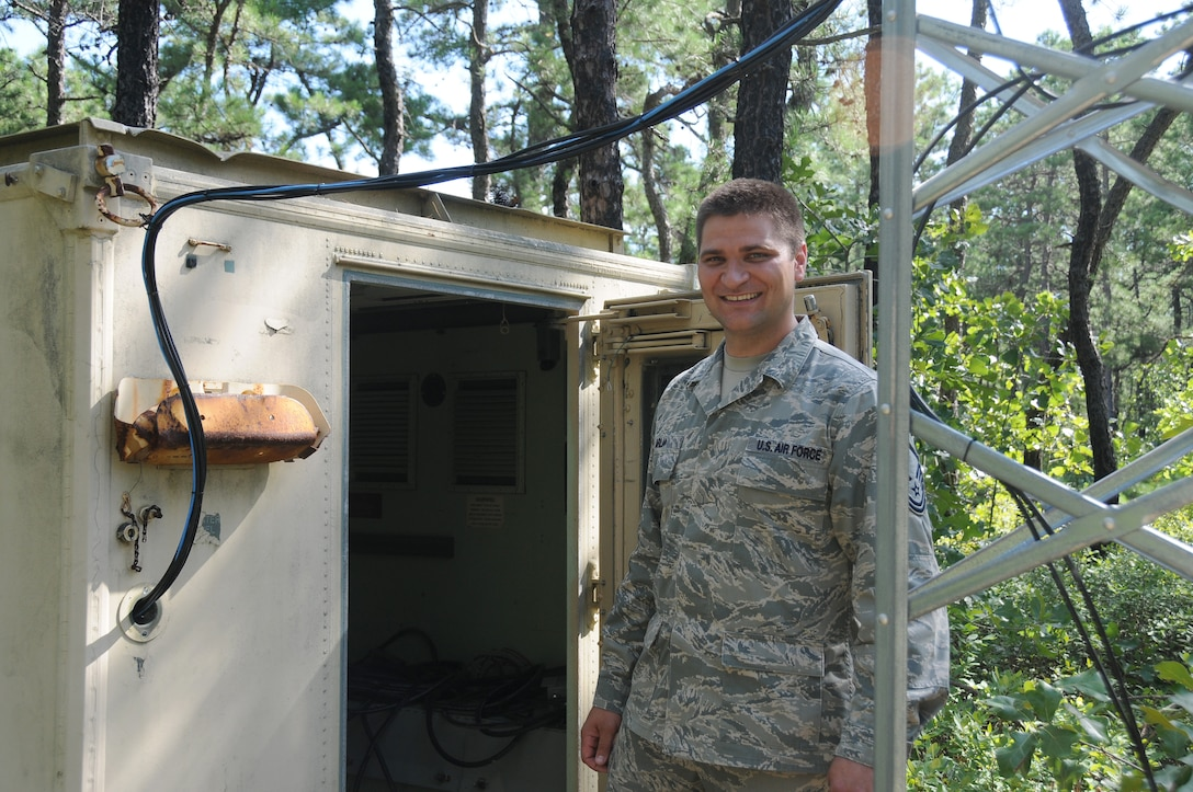 U.S. Air Force Master Sgt. Samuel Arlia stands outside of the structure the solar charging system he created to power multiple security camera towers at the 177th Fighter Wing's Warren Grove Gunnery Range detachment, New Jersey on July 23, 2015. (U.S. Air National Guard photo by Senior Airman Amber Powell/Released)