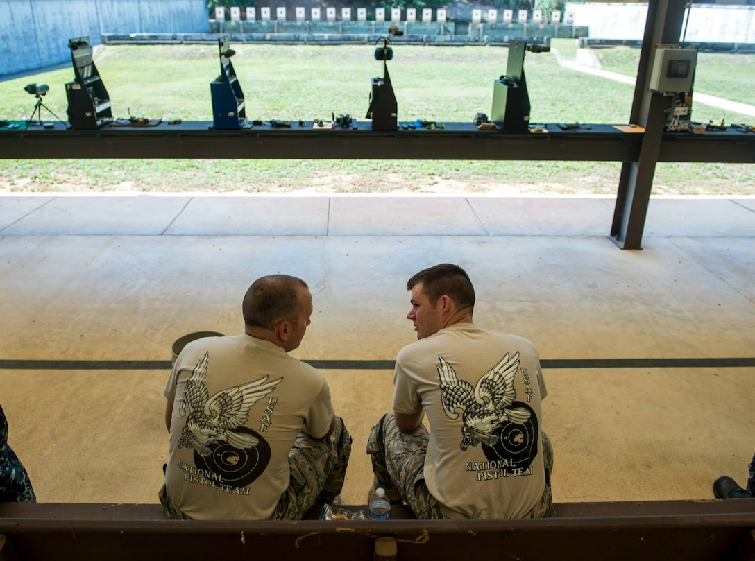 Second Lt. Tucker Sears (right), a 436th Logistics Readiness Squadron material management officer in charge, and his brother, Staff Sgt. Terrence Sears, the Air Force National Pistol Team NCO in charge, speak between matches at the Annual Interservice Pistol Championships June 8, 2015, at Fort Benning, Ga. The team placed fifth out of 13 teams and was Tucker's first competition while on the team. (U.S. Air Force photo/Staff Sgt. Andrew Lee)