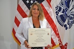 Defense Logistics Agency Energy Chief and Program Manager of Installation Energy's Renewables and Energy Savings Performance Based Contracting Laurie Carlson stands with her diploma from the National Defense University where she earned a Master of Science from the Dwight D. Eisenhower School and a Senior Acquisition Certificate from the Defense Acquisition University June 18.