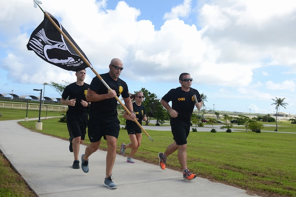 Members of the U.S. Air Force Office of Special Investigations Detachment 602 run during the Prisoner of War and Missing in Action vigil run Sept. 18, 2015 at Andersen Air Force Base, Guam. Airmen from multiple squadrons ran in one-hour shifts during the 24 hour run which began Sept 17. (U.S. Air Force photo by Airman 1st Class Arielle Vasquez/Released)