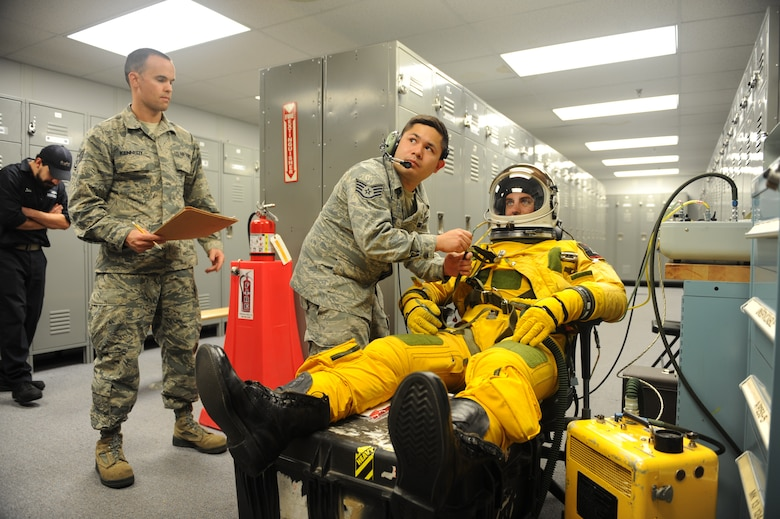 Staff Sgt. Timothy Dayrit (center), and Staff Sgt. Joseph Kennedy (left), 9th Physiological Support Squadron full-pressure suit technicians perform pre-flight full-pressure suit maintenance for Capt. Travis, 99th Reconnaissance Squadron U-2 pilot, Sep. 19, 2015, at Joint Base Andrews, Maryland. The full-pressure is worn by U-2 Dragon Lady pilots who frequently fly at the edge of space. (U.S. Air Force photo by Senior Airman Bobby Cummings)