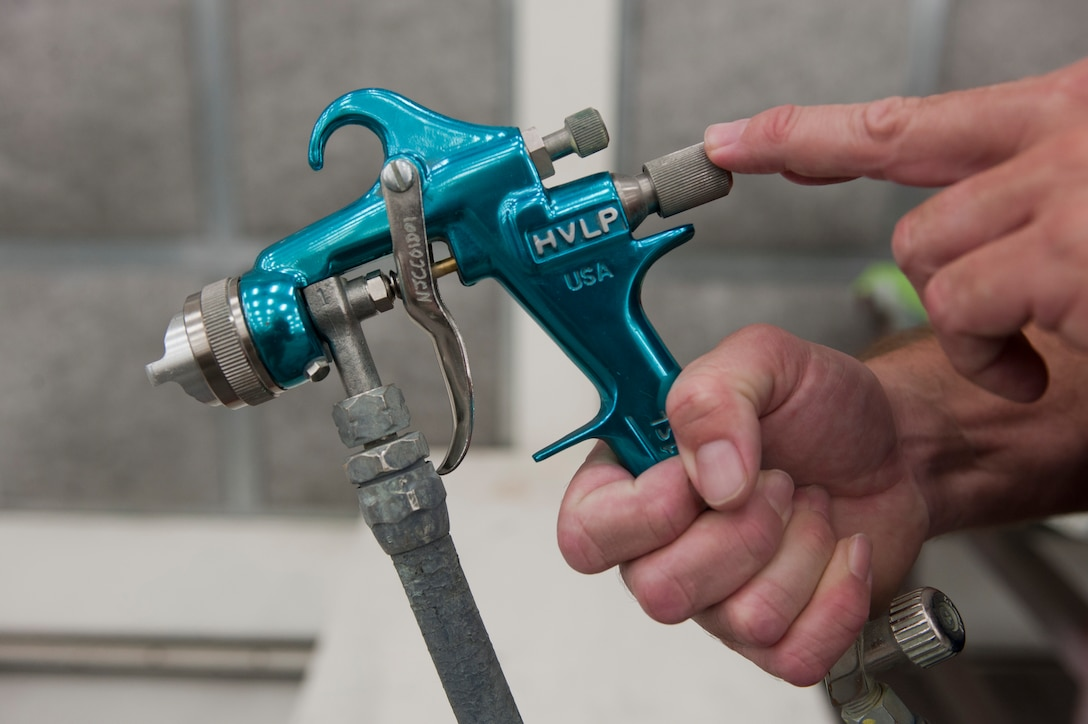 Jeff Dezell, 57th Maintenance Group Corrosion shop lead, holds a spray gun used to paint aircraft inside a temperature-controlled building on Nellis Air Force Base, Nev., Sept. 9, 2015. The corrosion shop assigns four people to work on each shift. (U.S. Air Force photo by Airman 1st Class Mikaley Kline)