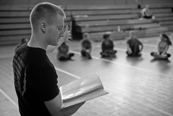 U.S. Air Force Staff Sgt. Matthew McConnell, 83rd Network Operations Squadron Detachment 4 plans and integration NCO and deputy director of Kaiserslautern Military Community Gracie Defense System, Ramstein Air Base, Germany, conducts a safety brief at the beginning of a self-defense class Sept. 15, 2015, at the Northside Fitness Center on RAF Mildenhall, England. Safety briefings are conducted at the beginning of each class to ensure all participants are aware of the risks, safety procedures and protocols involved during the training session. (U.S. Air Force photo by Staff Sgt. Micaiah Anthony/Released)