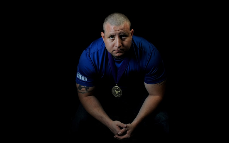 Tech. Sgt. David Hernandez, 509th Logistics Readiness Squadron resource advisor assistant, wears his gold medal Sept. 9, 2015, at Whiteman Air Force Base, Mo. He earned first place in a power lifting event at a competition with other wounded warriors. (U.S. Air Force photo illustration by Airman 1st Class Michaela R. Slanchik/Released)