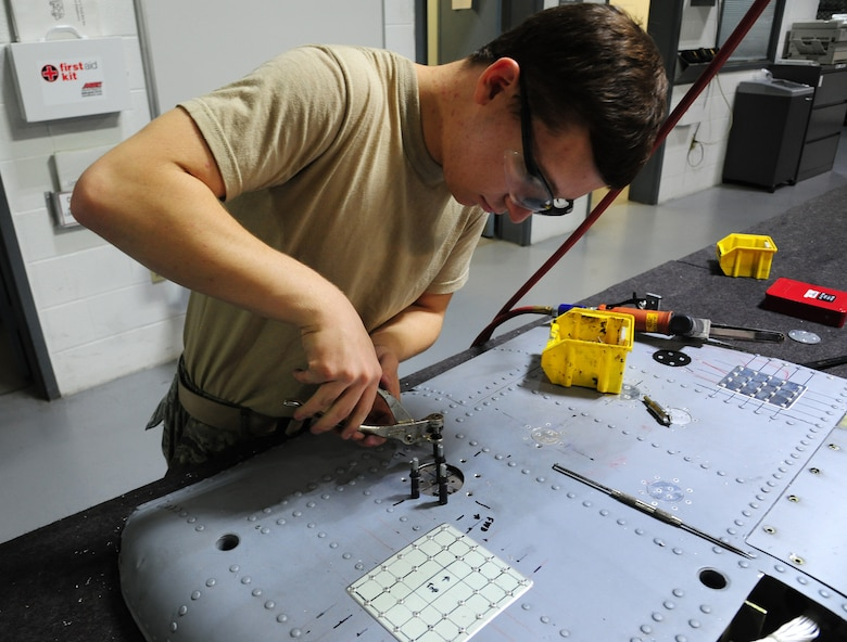 U.S. Air Force Airman 1st Class Logan Gutierrez, 509th Maintenance Squadron low observable trainee, performs a flush repair on an aircraft part at Whiteman Air Force Base, Mo., Sept. 15, 2015. Flush repairs are done to restore punctures on aircraft parts, preventing the metal from loosening or corroding. (U.S. Air Force photo by Senior Airman Keenan Berry/Released)