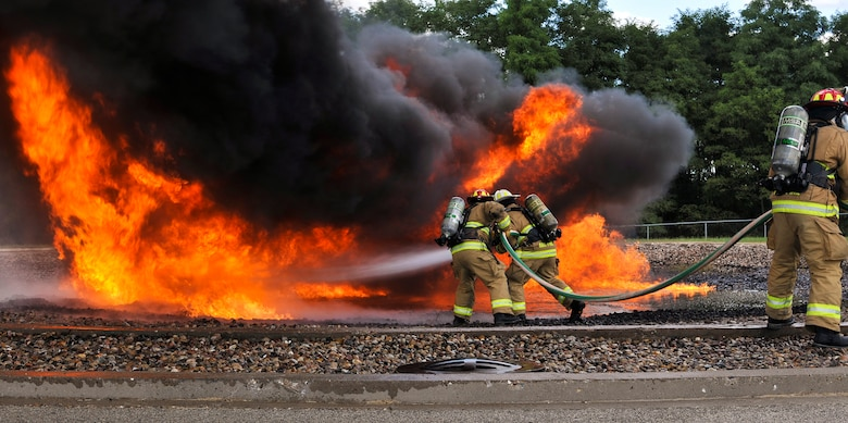 Fire protection specialists with the 182nd Civil Engineer Squadron, Illinois Air National Guard, demonstrate how they extinguish jet fuel fires during a controlled burn at Wingman and Family Day at the 182nd Airlift Wing, Peoria, Ill., Sept. 12, 2015. The event was organized to promote resiliency in Airmen and their friends and family. (U.S. Air National Guard photo by Staff Sgt. Lealan Buehrer/Released)