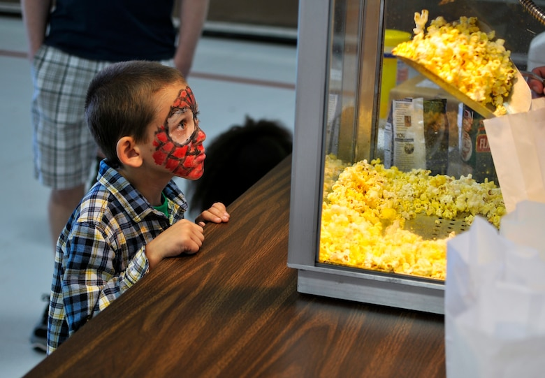 Timothy, son of a 182nd Airlift Wing technical sergeant, watches his bag of popcorn get filled during Wingman and Family Day at the 182nd Airlift Wing, Peoria, Ill., Sept. 12, 2015. The event was organized to promote resiliency in Airmen and their friends and family. (U.S. Air National Guard photo by Staff Sgt. Lealan Buehrer/Released)