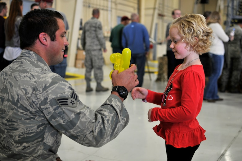 U.S. Air Force Senior Airman Lance A. Liggett, tactical air control party specialist with the 169th Air Support Operations Squadron, Illinois Air National Guard, makes Mallory an animal balloon during Wingman and Family Day at the 182nd Airlift Wing, Peoria, Ill., Sept. 12, 2015. The event was organized to promote resiliency in Airmen and their friends and family. (U.S. Air National Guard photo by Staff Sgt. Lealan Buehrer/Released)