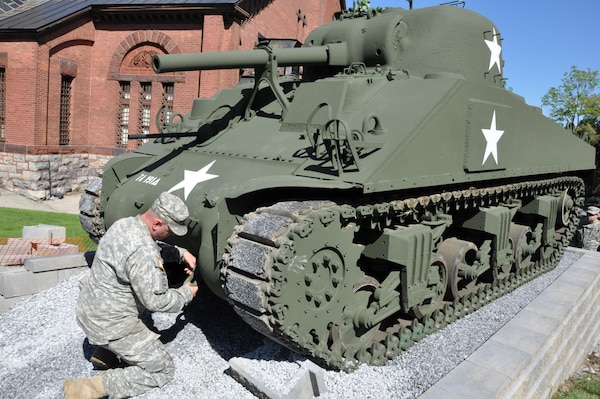 New York Army National Guard Spc. Jonathon Bishop, Co. B, 427th Brigade Support Battalion, attaches a clevis fastener on a refurbished World War II-era M4A3 Sherman tank on permanent display at the New York State Military Museum in Saratoga Springs, Sept. 15, 2015. National Guard Soldiers working full time at the Maneuver Area Training Equipment Site, or MATES, at Fort Drum, spent the past 22 months refurbishing and repainting the tank in their spare time.