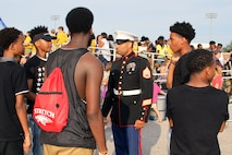 U.S. Marine Corps Staff Sgt. Ivory Carter III, a recruiter at Recruiting Sub-Station Cincinnati, engages a group of high school students during a football game at Walnut Hills High School, Aug. 28, 2015. Carter serves as a resource of information about the Marine Corps in the local community to provide young people with a promising opportunity after the completion of high school. (U.S. Marine Corps photo by Sgt. Jennifer Pirante/Released)