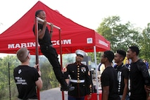 Quaris Gardner, a student at Walnut Hills High School, performs pull-ups during the Marine Corps Pull-Up Challenge at Walnut Hills High School, Aug. 28, 2015.The Walnut Hills Eagles took on the Woodward Bulldogs during the U.S. Marines Battle of the Grid Iron Tour and took home the first Ohio victory of the season with a score of 23-0. (U.S. Marine Corps photo by Sgt. Jennifer Pirante/Released)