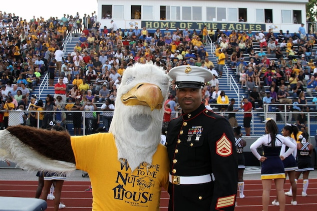 U.S. Marine Corps Staff Sgt. Ivory Carter III, recruiter at Recruiting Sub-Station Cincinnati, poses for a photo with the Walnut Hills Eagles mascot during a high school football game at Walnut Hills High School, Aug. 28, 2015. The Walnut Hills Eagles took on the Woodward Bulldogs during the U.S. Marines Battle of the Grid Iron Tour and took home the first Ohio victory of the season with a score of 23-0. (U.S. Marine Corps photo by Sgt. Jennifer Pirante/Released)