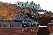 U.S. Marine Corps Staff Sgt. Ivory Carter III, Marine recruiter at Recruiting Sub-Station Cincinnati, gets the crowd riled up during a high school football game at Walnut Hills High School, Aug. 28, 2015. The Walnut Hills Eagles took on the Woodward Bulldogs during the U.S. Marines Battle of the Grid Iron Tour and took home the first Ohio victory of the season with a score of 23-0. (U.S. Marine Corps photo by Sgt. Jennifer Pirante/Released)