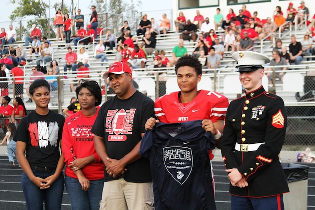 Sean Mahone, high school senior and cornerback for the Lakota West High School Firebirds, receives his Semper Fidelis All-American Bowl selection jersey before the kick-off of a football game against the Princeton Vikings Sept. 18, 2015. The Semper Fidelis Football Program focuses on mentoring exceptional youth athletes and future leaders by collectively celebrating academic excellence, proven physical fitness and quality of character. It also serves as an extension of the Marine Corps focus on developing quality citizens and reinforcing the value of public service. (U.S. Marine Corps photo by Sgt. Jennifer Pirante/Released)