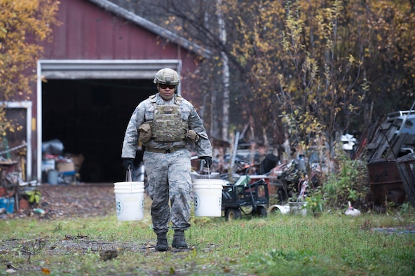 Tech. Sgt. Michael Alexander II, a 354th Civil Engineer Squadron explosive ordinance disposal technician from Eielson Air Force Base, Alaska, removes two of four buckets containing 65 sticks deteriorating dynamite from a garage in Delta Junction, Alaska, Sept. 20, 2015. The EOD flight responded to the report of explosives at the request of local authorities. (U.S. Air Force photo/Staff Sgt. Shawn Nickel)