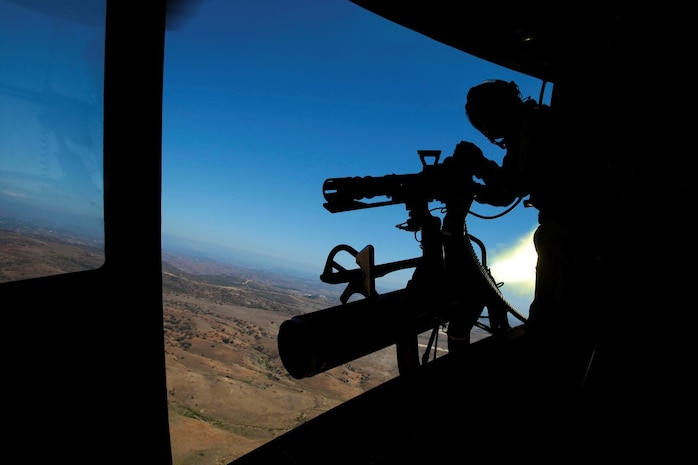 Donnelly, Idaho, native, Sgt. Elizabeth Azcuenaga, an enlisted aircrew training manager with Marine Light Attack Helicopter Squadron 169 (HMLA-169), Marine Aircraft Group 39, 3rd Marine Aircraft Wing, I Marine Expeditionary Force, fires a GAU-17 machine gun from the door of a UH-1Y Huey while the pilot simultaneously launches a rocket aboard Marine Corps Base Camp Pendleton, Calif., Sept. 17, 2015. Azcuenaga fired the weapon during a weapons proficiency range designed to help new pilots and crew chiefs become more effective with their respective weapons systems. (U.S. Marine Corps photo by Lance Cpl. Caitlin Bevel)