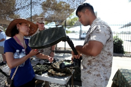 An explosive ordnance disposal Marine explains how a metal detector works to an onlooker during San Diego Fleet Week 2015 aboard Naval Base Coronado, Calif., Sept. 20, 2015. Thirty-seven Marines from 7th ESB presented static displays during the event to demonstrate the quality of military assets to the citizens of San Diego.