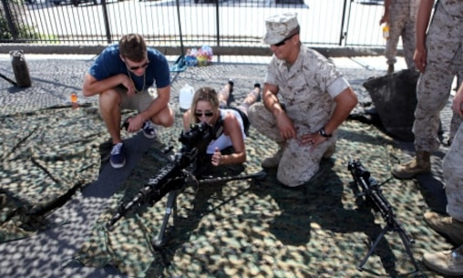 Lance Cpl. Matthew Ritter, a heavy equipment operator with Bulk Fuel Company, 7th Engineer Support Battalion, shows a couple a weapons system during San Diego Fleet Week 2015 aboard Naval Base Coronado, Calif., Sept. 20, 2015. Thirty-seven Marines from 7th ESB presented static displays during the event to demonstrate the quality of military assets to the citizens of San Diego.