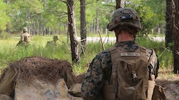 Lance Cpl. Cody Conlon, a fireteam leader with 2nd Marine Regiment, watches Marines with his unit set up defenses from his fighting position during a battalion deployment for training exercise aboard Camp Lejeune, N.C., Sept. 16, 2015. The defensive training took place during a nine-day deployment for training exercise designed to prepare for a variety of combat scenarios, including defensive, offensive, and urban operations.