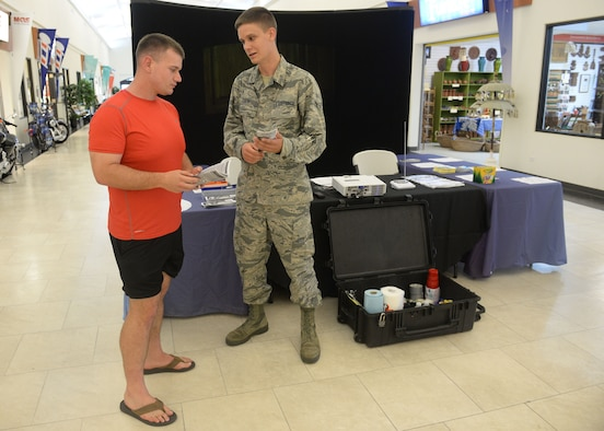 Airman Brian Tripp, 36th Civil Engineer Squadron emergency management apprentice, speaks with a Team Andersen member Sept. 22, 2015, at Andersen Air Force Base, Guam. Emergency managers set up a static display and informed base exchange patrons about Andersen AFB disaster response and recovery operations during National Preparedness Month. (U.S. Air Force photo by Senior Airman Joshua Smoot/Released)