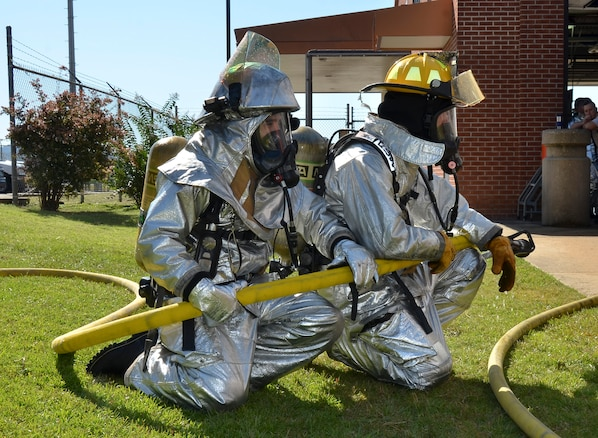 """Firefighters from the Civil Engineering Squadron practice fighting structure fires as a part of their annual training at the 117th Air Refueling Wing on September 19, 2015. The firefighters used a travel trailer and other equipment to simulate structure fires caused by propane gas. According to Master Sgt. Brian Garvich, their main strategy in fighting these fires was to utilize the """"two-in, two-out"""" policy which mandates that firefighters never enter a building alone during a rescue mission. Two firefighters act as a team entering the structure and another two-person team is waiting outside the hazard dedicated to rescuing those inside, should they need it. (U.S. Air National Guard photo  by Staff Sgt. Jeremy Farson/Released)"""