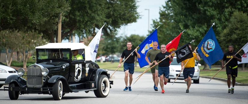 Chief Master Sgt. Kristopher Berg, 437th Airlift Wing command chief, leads the way with the POW/MIA flag during the end of the 24 hour Vigil Run Sept. 18, 2015. The ceremony at the base flagpole on Joint Base Charleston – Air Base, S.C. included a 21-gun salute by the Honor Guard, a wreath-laying and a live bugle performance in recognition of captured and missing U.S. servicemembers. (U.S. Air Force photo/Airman 1st Class Clayton Cupit)