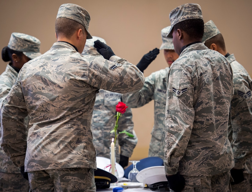 A Joint Base Charleston Honor Guard team salutes the POW/MIA table Sept. 18, 2015, at the Charleston Club on JB Charleston – Air Base, S.C. The POW/MIA table is symbolic of members of the armed forces who have become prisoners of war in foreign countries as well as those who are missing and unaccounted for. (U.S. Air Force photo/Airman 1st Class Clayton Cupit)