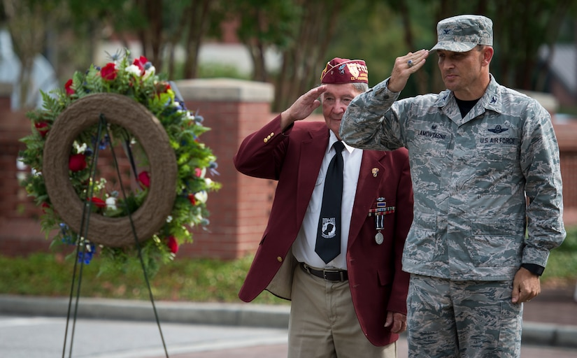 Col. John Lamontagne, 437th Airlift Wing commander and Reggie Salisbury, A U.S. Army infantry veteran, D-Day survivor and World War II prisoner of war salute after laying a wreath during the POW/MIA retreat ceremony Sept. 18, 2015, at the base flagpole on Joint Base Charleston – Air Base, S.C. The ceremony also included a 21-gun salute by the Honor Guard and a live bugle performance in recognition of captured and missing U.S. servicemembers. (U.S. Air Force photo/Airman 1st Class Clayton Cupit)