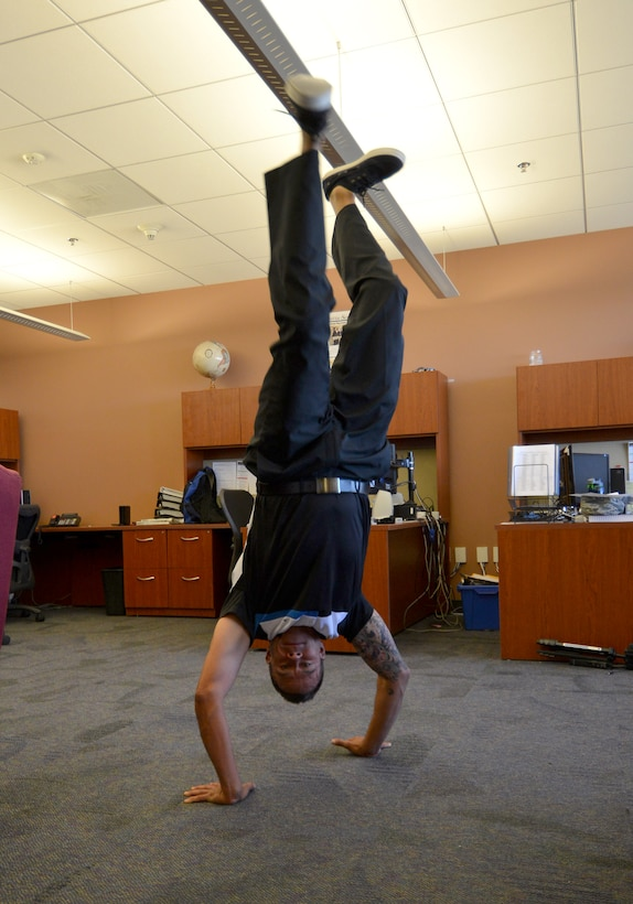 Frank Vigil, 50th Space Wing chief of information protection, does a hand stand in Building 210 Wednesday, Sept. 16, 2015, at Schriever Air Force Base, Colorado. Vigil believes in happiness and creating a positive work environment for himself and those who work for him. (U.S. Air Force photo/Staff Sgt. Debbie Lockhart)