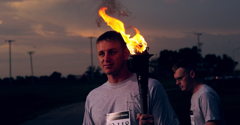 A member of Team Whiteman holds the ceremonial torch as the runners prepare for a 24-hour Prisoners of War/Missing in Action run at Whiteman Air Force Base, Mo., Sept.18, 2015. Congress has designated the third Friday of September as a day to commemorate the POWs and Service members missing in action. (U.S. Air Force photo by Airman 1st Class Jovan Banks/Released)