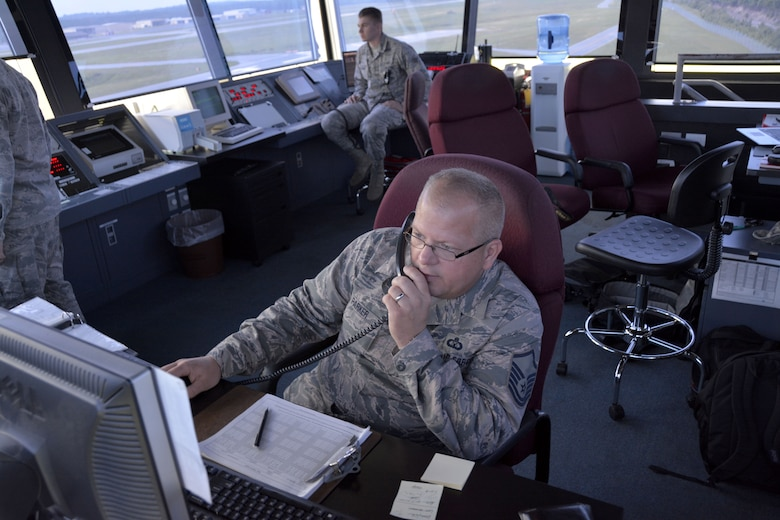 235th Air Traffic Control Squadron, Tower Watch Supervisor, Master Sgt. Tony L. Parker, makes entries in the daily event log as Senior Airman James D. Bellissimo, ground controller; surveys taxi ways at Stanly County Airport, New London, N.C., July 8, 2015. The 235th ATCs provides air traffic control services for all civilian and military aircraft at the Stanly County Airport, New London, N.C. (U.S. Air National Guard photo by Master Sgt. Patricia F. Moran, 145th Public Affairs/Released)