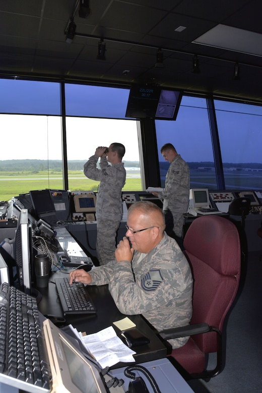 U.S. Air Force Master Sgt. Tony L. Parker, tower watch supervisor for the 235th Air Traffic Control Squadron issues a Notice to Airmen (NOTAM) with Lockheed Martin Flight Services for C-130 aircraft night operations training as Staff Sgt. Justin W. Condon, a local controller for airborne aircraft looks for aircraft arriving from the east. Senior Airman James D. Bellissimo, ground controller, consults regulations for a precision approach radar alignment during daily operations, July 8, 2015 at Stanly County Airport, New London, N.C. (U.S. Air National Guard photo by Master Sgt. Patricia F. Moran, 145th Public Affairs/Released)