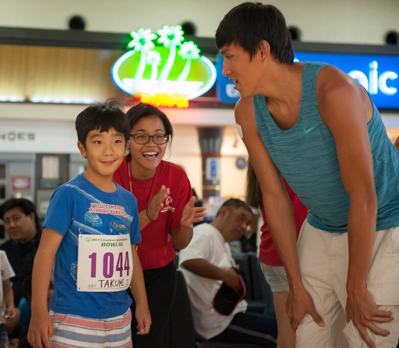 Shawn Monroe and Takara Maruo, high school students, congratulate Takumi, Kadena Special Olympics athlete, on bowling a strike during the KSO bowling event at Enagic Bowling in Mihama, Japan, Sept. 19, 2015. More than 300 people including athletes and their families packed into the bowling center to compete and cheer on their athletes. (U.S. Air Force photo by Airman 1st Class Corey M. Pettis)