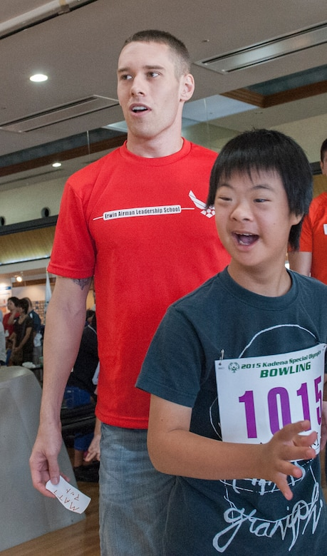 U.S. Air Force Staff Sgt. Matt Burns, 18th Wing Professional Military Education Center Airman Leadership School instructor, and Yuzuki, Kadena Special Olympics athlete, watch the bowling ball roll down the lane during the KSO bowling event at Enagic Bowling in Mihama, Japan, Sept. 19, 2015. Bowling kicks off KSO as the first competition in a series of many events. (U.S. Air Force photo by Airman 1st Class Corey M. Pettis)