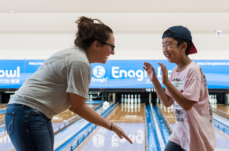 U.S. Air Force Staff Sgt. Rachel McCoy, 18th Logistic Readiness Squadron central storage supervisor, and Yuto, Kadena Special Olympics Athlete, high five each other after Yuto rolls the bowling ball during the KSO bowling event at Enagic Bowling in Mihama, Japan, Sept. 19, 2015. Airmen from Kadena Air Base volunteered to fill each lane and assist the athletes as they bowled. (U.S. Air Force photo by Airman 1st Class Corey M. Pettis)