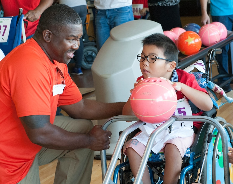 U.S. Air Force Master Sgt. Cedric Smith, 18th Equipment Maintenance Squadron aerospace ground equipment production superintendent, helps Yuko, Kadena Special Olympics athlete, push the ball off of the ramp during the KSO bowling event at Enagic Bowling in Mihama, Japan, Sept. 19, 2015. Athletes shared the lane with two others as they took turns to bowl two games. (U.S. Air Force photo by Airman 1st Class Corey M. Pettis)