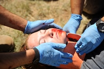 Emergency medical technicians from Joint Base San Antonio- Fort Sam Houston, Texas, assess and treat a patient during a scenario in the EMT Rodeo Sept. 18, 2015, at Melrose Air Force Range, N.M.. Twenty-one teams of elite EMTs from 22 installations across the Air Force convened at Cannon for four days of innovative, high-octane competition Sept. 16-19. Throughout the rodeo teams were required to execute their lifesaving mission under the critical eye of expert evaluators, demonstrating accurate technique and effective implementation. (U.S. Air Force photo/Tech. Sgt. Manuel J. Martinez)