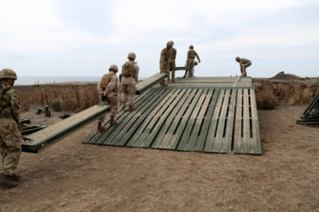 Engineers from Bridge Company, 7th Engineer Support Battalion, 1st Marine Logistics Group and 1st Combat Engineer Battalion, 1st Marine Division as well as members of British 54 Commando Squadron Royal Engineers move deck pieces into place on a medium girder bridge aboard Camp Pendleton, Calif., Sept. 21, 2015. Marines from 7th ESB and 1st CEB are conducting various engineer training events alongside their British counterparts in coming weeks as part of annual large-scale exercise Black Alligator.
