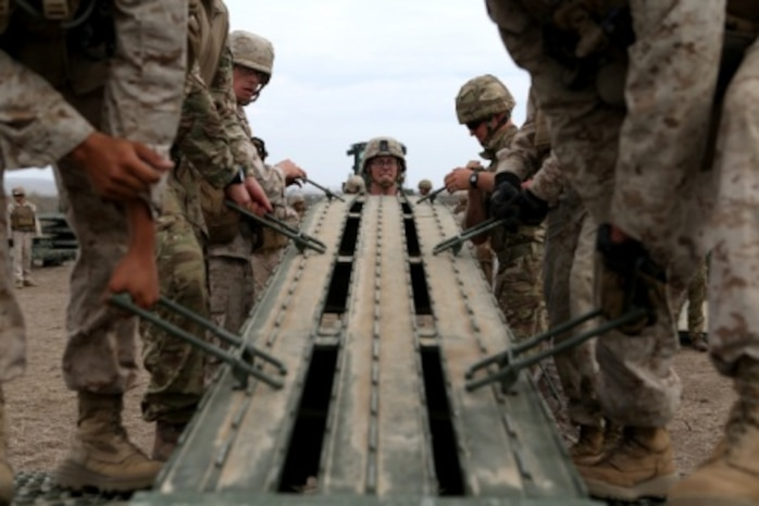 Engineers from Bridge Company, 7th Engineer Support Battalion, 1st Marine Logistics Group and 1st Combat Engineer Battalion, 1st Marine Division work with members of British 54 Commando Squadron Royal Engineers to place a ramp on a medium girder bridge aboard Camp Pendleton, Calif., Sept. 21, 2015. Marines from 7th ESB and 1st CEB are conducting various engineer training events alongside their British counterparts in coming weeks as part of annual large-scale exercise Black Alligator.