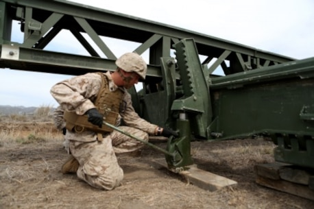 Cpl. James Stroeher, a combat engineer with Bridge Company, 7th Engineer Support Battalion, 1st Marine Logistics Group uses a 20-ton jack to lift the end of a medium girder bridge so other engineers can form a stabilizing platform for the massive bridge aboard Camp Pendleton, Calif., Sept. 21, 2015. Marines from 7th ESB and 1st Combat Engineer Battalion, 1st Marine Division are conducting various engineer training events alongside British Royal Engineers from the 54 Commando Squadron in coming weeks as part of annual large-scale exercise Black Alligator.