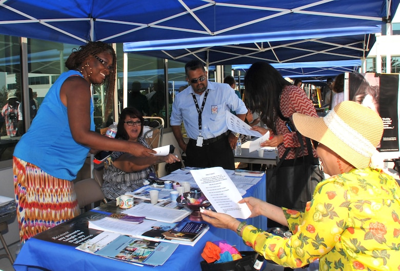 Sheila Harris, 61st Communications Squadron, hands out information at one of the booths during the 2015 Space and Missile Systems Center's Diversity Day event, Sept. 23 at Los Angeles Air Force Base in El Segundo, Calif.   (U.S. Air Force photo/Sarah Corrice)